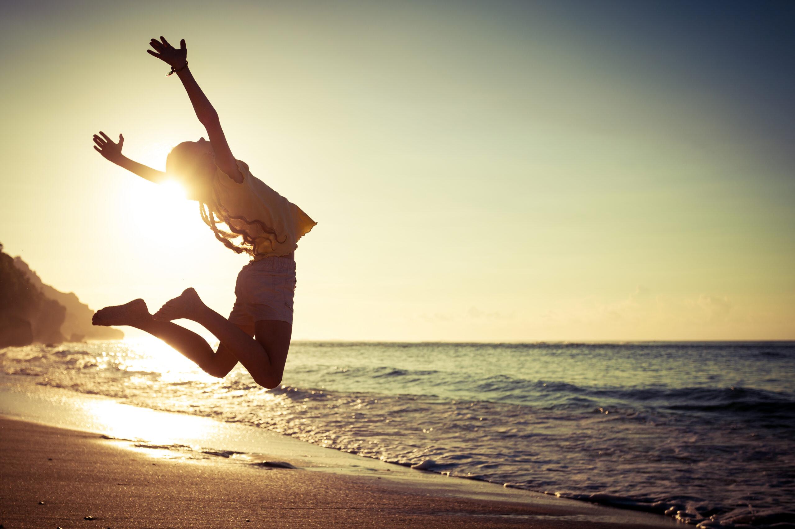 chica feliz saltando en una playa
